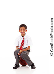 primary schoolboy sitting on basket ball