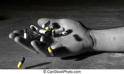 Mans hand falling holding pills after overdose in selective...