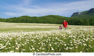 Among flowers - Father and daughter on a walk in a blooming...