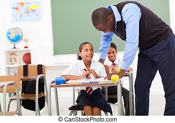 elementary teacher helping student in classroom