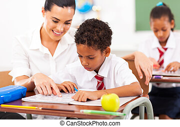 caring elementary school teacher helping student in...