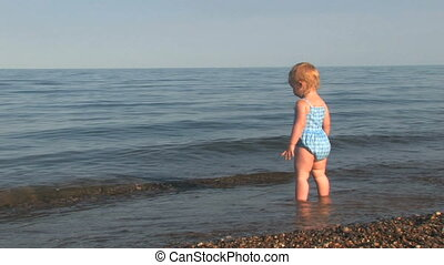 Beach Baby 2 - 20 month old girl stands on a pebble shore...