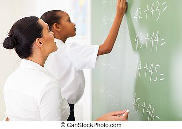 primary school maths teacher teaching student in classroom