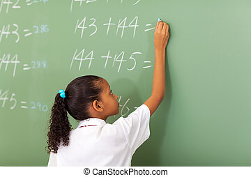 school girl writing maths answer - primary school girl...