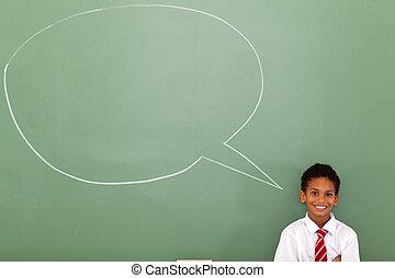 elementary schoolboy with speech bubble drawn on chalkboard