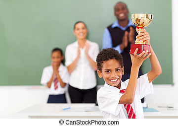 elementary school student holding a trophy - happy male...