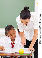 primary school educator tutoring student - beautiful female...
