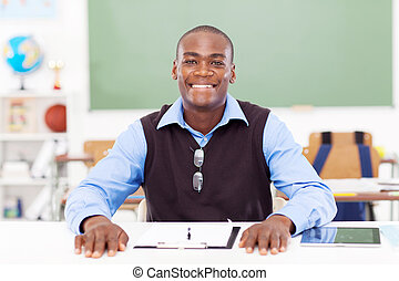 African male teacher sitting in classroom - African male...