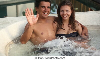 In jacuzzi - Happy lovers hugging and laughing in jacuzzi