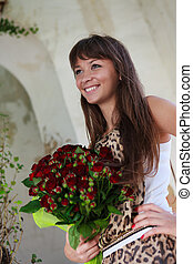 Beautiful smiling woman with a bouquet of red roses