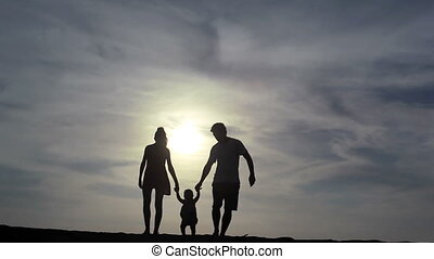 Family - Silhouette of family walking together at summer