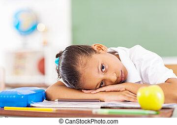 primary schoolgirl lying in classroom - primary schoolgirl...