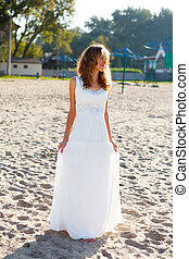 Young smiling woman bride in a white dress on the sunny...