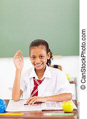 primary schoolgirl hand up in classroom
