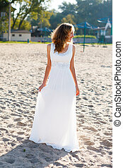 Beautiful laughing woman bride in a white dress on the sunny...
