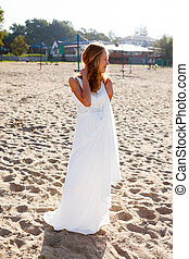 Beautiful smiling girl bride in a white dress on the sunny...