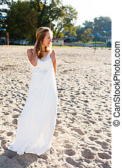 Girl bride in a white dress on the sunny beach