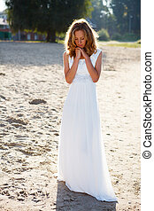 Romantic girl bride in a white dress on the sunny outdoor...