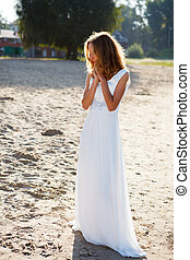 Dear girl bride in a white dress on the sunny outdoor Bright...
