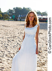 Pretty girl bride in a white dress on the sunny beach...