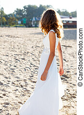 Girl bride in a white dress on the sunny beach half-turned...