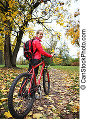 Woman cyclist with bike and backpack bicycle walk in park