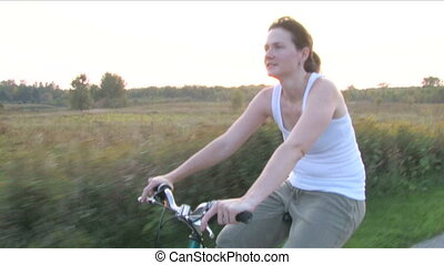 Woman on Bike Ride 3 - Moving alongside a young woman riding...