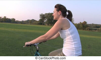 Woman on Bike Ride 5 - Moving alongside a young woman riding...