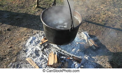 Pot Over Fire - Two shots A large cauldron of steaming...