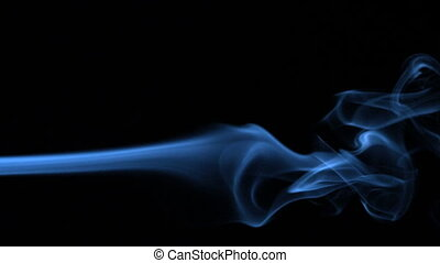 Blue smoke blowing across black background in slow motion