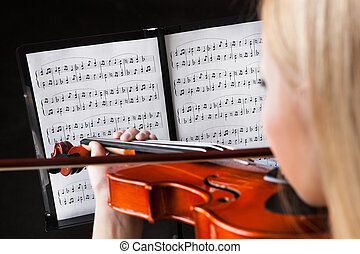 Beautiful young woman playing violin over black background