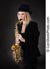 Beautiful young woman playing saxophone over black...