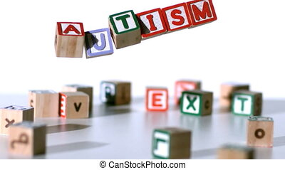Blocks spelling autism falling in slow motion