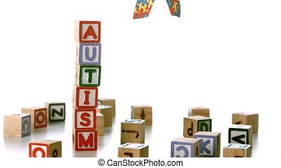 Autism ribbon falling beside blocks spelling autism in slow...