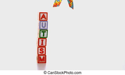 Awareness ribbon dropping beside blocks spelling autism in...