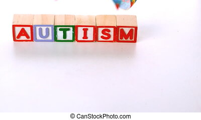 Awareness ribbon falling in front of autism letter blocks in...