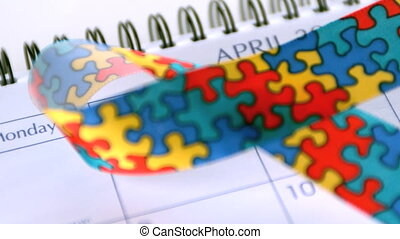 Awareness ribbon falling on calendar marking awareness day...