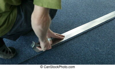 Cutting the carpet under the ruler - Cutting the carpet...