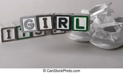Its a girl message in letter blocks beside booties in slow...