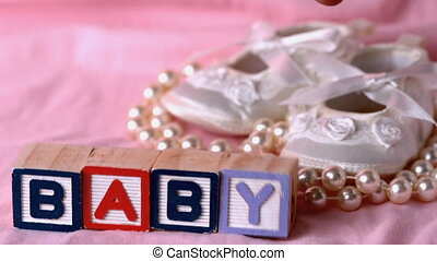 Baby in letter blocks beside booties and pearls on pink...