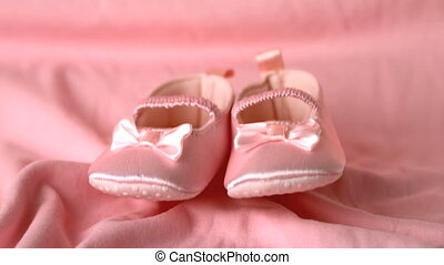 Pink booties falling on pink blanke