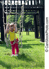 happy little girl playing on park playground