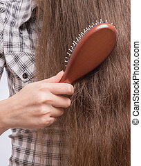 Woman combs her hair - Young beautiful woman combing her...