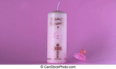 Pink pacifier falling beside baptism candle on pink...