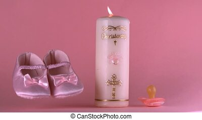 Baby shoes falling beside lit baptism candle and pacifier in...