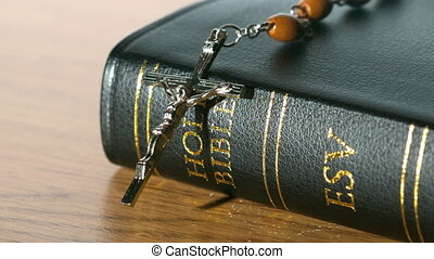Rosary beads falling onto bible on a table in slow motion