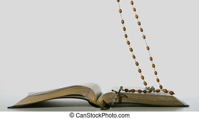 Rosary beads falling onto open bible on white background in...