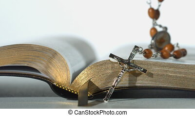 Rosary beads falling on open bible on white background close...