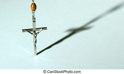 Rosary beads casting a shadow and then falling in slow...
