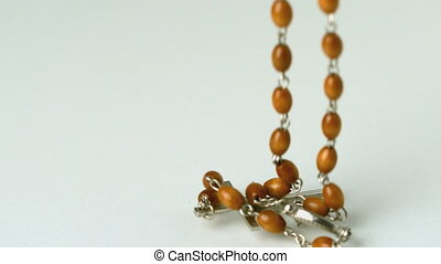 Rosary beads falling on white surface in slow motion